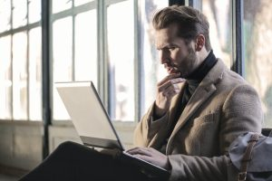 Confused Man Looking at Laptop